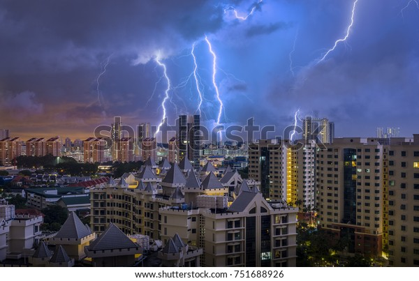 Tropical thunderstorm over apartment buildings in Singapore. Several flashes hitting the buildings in the distance.