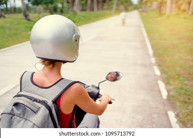 Tropical travel and transport. Woman in helmet riding scooter on the road.