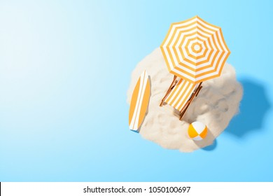 Tropical vacation background. Sun lounger with umbrella and beach accessories for active rest on the sandy island, copy space, top view