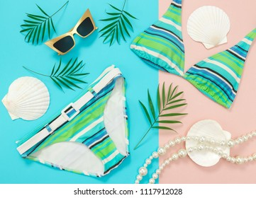 Tropical vacation flat lay on turquoise and pink background. Summer fashion.