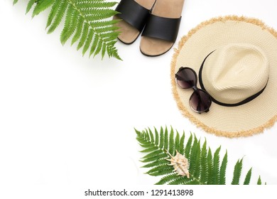 Tropical vacation outfit. Straw beach sunhat, sun glasses, beach slaps, leaf of fern on white. Top view with copy space. Summer.