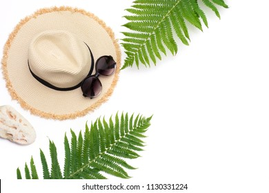 Tropical vacation. Straw beach sunhat, sunglasses, leaf of fern on white background. Top view with copy space. Summer concept.