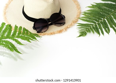 Tropical vacation. Straw beach sunhat, sun glasses, leaf of fern on white. Copy space. Summer concept.