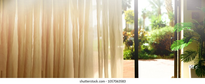 Tropical view background. Summer, travel, vacation and holiday concept. Open window, door and white curtain with blurred palm garden view from hotel. Exotic plants in sunny day, copy space. Banner.