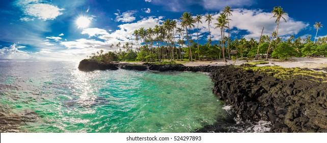 Tropical volcanic beach with sun reflection on Samoa Island with many palm trees