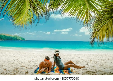 Tropical white beach at Praslin island Seychelles, happy Young couple man and woman during vacation Holiday at the beach relaxing under a palm tree