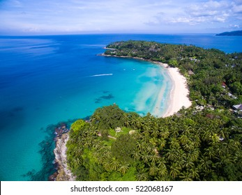 Tropical white sand beach with azure clear water, lush greenery and granite stones. Top view. Aerial shooting of Pansee beach, Phuket, Thailand