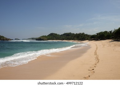 tropical white sand shore with foot prints at wediombo, java island, indonesia