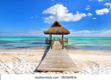 Tropical white sandy beach. Palm leaf roofed wooden pier with gazebo on the beach. Punta Cana, Dominican Republic