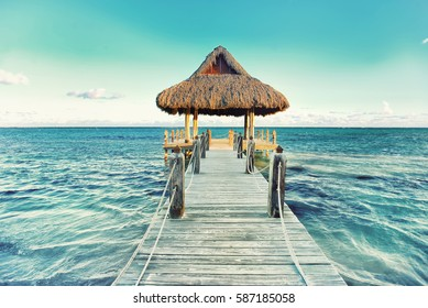 Tropical white sandy beach. Palm leaf roofed wooden pier with gazebo on the beach. Punta Cana, Dominican Republic. Instagram filter