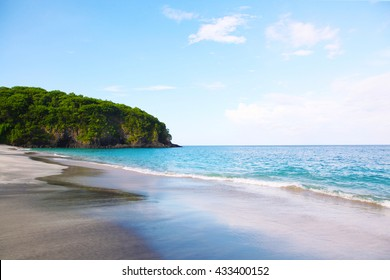 Tropical white sandy beach with rocky mountains and clear water of Indian ocean in Bali.