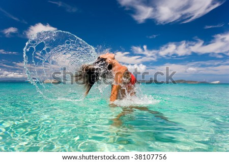 tropical woman flips hair in turquoise waters