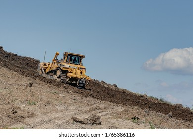 Trossingen, Germany, June 25, 2020. On the way to heaven. Caterpillar bulldozer, working the soil on a steep mound of earth on the earth dump of the city of Trossingen.