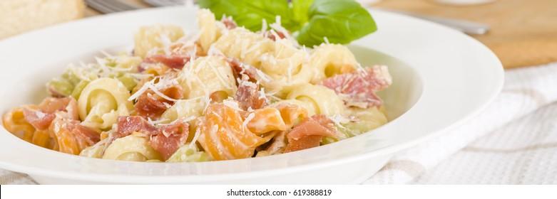 Trottole Tricolore Panna e Prosciutto - Italian tricolour pasta with creamy sauce and parma ham garnished with parmigiano reggiano.