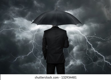 Trouble ahead, businessman with umbrella standing in front of a stormy sky