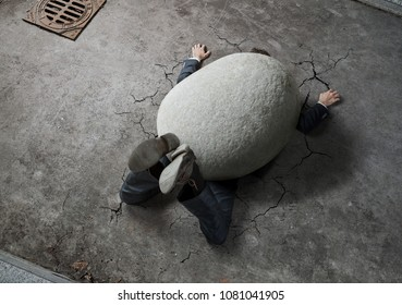 Trouble, crisis concept, high angle view of businessman crushed by the huge stone on the street with copy space