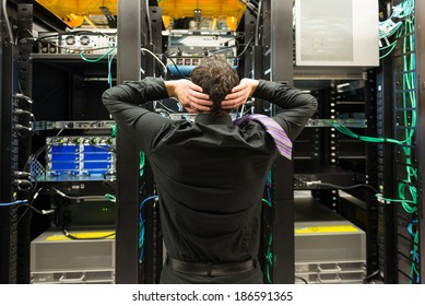 Trouble in data center. Man looking astonished in a network data center.