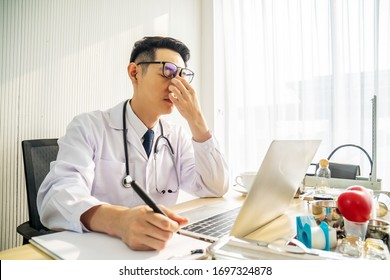 Troubled asian man doctor working on computer at desk in hospital clinic, worried, thinking hard, healthcare concept for Covid19.