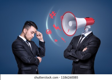 A troubled businessman stands near another man with a large shouting megaphone instead of his head. Getting reprimanded. Boss and employee. Reprimand and shame.