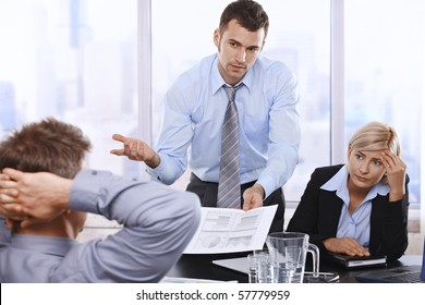 Troubled businesspeople discussing report at meeting, businessman showing document to boss with asking gesture.?