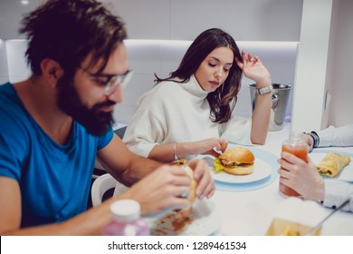 Troubled couple eating dinner with friends in the house