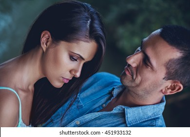 Troubled couple hugging sadly and looking down