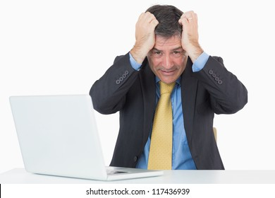Troubled man sitting at his desk with a laptop on a white background