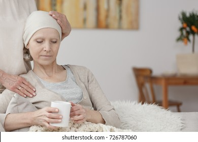 Troubled patient with cancer tumor holding a cup of tea while being comforted by a family member