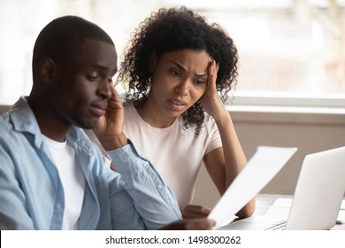 Troubled pensive biracial young couple feel disappointed consider paperwork paying bills online, sad frustrated mixed race ethnicity family upset having financial problems, stressed about bankruptcy