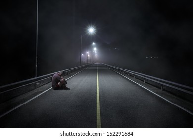 Troubled teenager boy with hidden face sitting in the night street