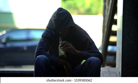 Troubled teenager drinking beer sitting on steps in gateway, lost in life