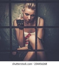 Troubled teenager girl behind bars showing middle finger