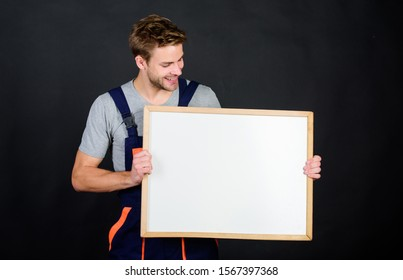 Troubleshoot and fix faulty electrical switches. Repairman engineer hold whiteboard copy space. Handsome repairman. Man repairman builder work clothes. Plan repair work using blueprints or diagrams.