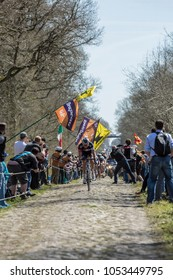 Trouee d'Arenberg,France - April 12,2015: The breakawaya approaching through a crowd of spectators in the famous cobblestoned road from the forest of Arenberg during the Paris Roubaix 2015 race.