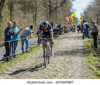 Trouee d'Arenberg,France - April 12,2015: The cyclist Aleksejs Saramotins of IAM Cycling Team riding on the famous cobblestone road from the forest of Arenberg during the Paris Roubaix 2015 race.