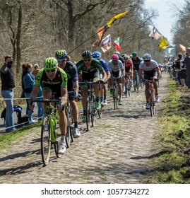 Trouee d'Arenberg,France - April 12,2015: The peloton riding on the famous cobblestone road from the forest of Arenberg during the Paris Roubaix 2015 race.