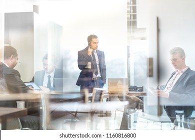 Trough glass window view of businessman executive talking on mobile phone in modern corporate office, holding financial newspaper. Reflection of business people working and meeting in other offices.