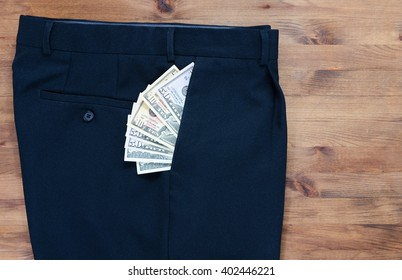 trousers and dollars in the pocket on old wooden table