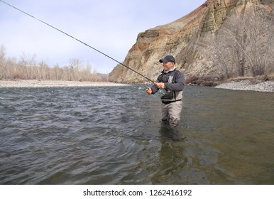trout fisherman casting on a river