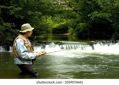 Trout fisherman standing in a pool of a stream