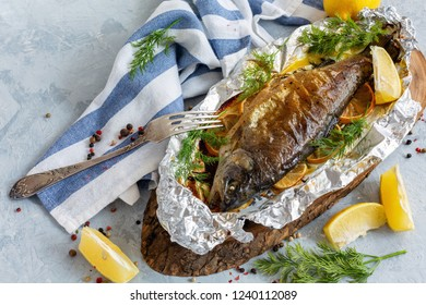 Trout with lemon, greens, pepper mixture baked in foil, selective focus.