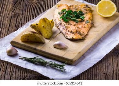 Trout steak with baked potatoes garlic, rosemary and vagetables on wooden board.