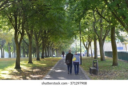 TROWBRIDGE, UK - OCT 14, 2015: A couple walk through a public park on Oct 25, 2015 in Trowbridge, UK. The UK experiencing an 'Indian Summer' with above average temperatures and stunning fall colours.