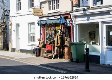 Trowbridge Wiltshire UK March 24 2020 A man sat in the sun outside an antiques and curiousity  shop with various items displayed on the pavement