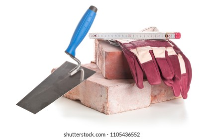 Trowel with bricks, folding rule and working gloves on white background - home construction or renovation concept