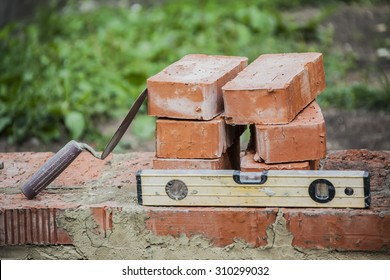 trowel and bricks lying on the basement of an unfinished house as a symbol of construction