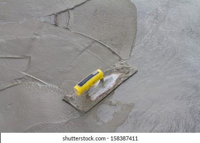 Trowel on fresh concrete at construction site