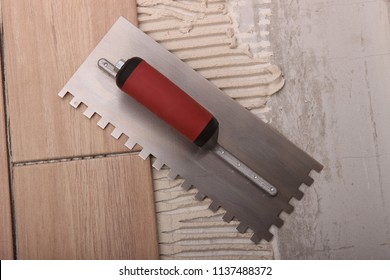 Trowel, thinset and hands