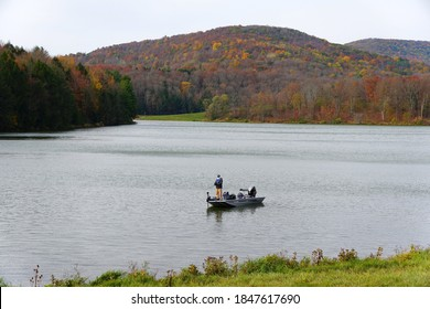 Troy, Pennsylvania, U.S.A - October 18, 2020 - A fisherman on the boat on the lake surrounded by striking color of fall foliage