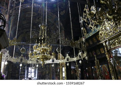 TROYAN, BULGARIA - APR 14, 2019 - Chandelier with frescoes on walls and Iconostasis separating nave from apse in Stauropegial Troyan monastery ,Troyan, Bulgaria